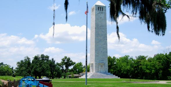 A white stone monument with an American flag flying on a flagpole nearby
